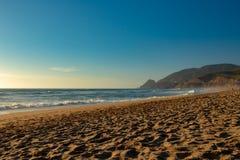 Guld- sandig strand på solnedgången på en sommarafton royaltyfri fotografi
