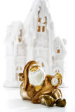 Guld- Santa Claus innehavklocka framme av vinterhuset Royaltyfria Bilder