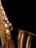 Guld- saxofon på mörk bakgrund arkivbilder