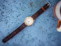 Guld-/silvertappningklocka med det bruna läderarmbandet arkivfoto