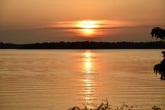 Guld- sjösolnedgång med solen som döljas delvist Fotografering för Bildbyråer