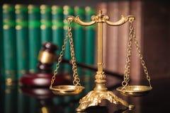 Guld- skala framme av domares auktionsklubba och lagböcker Royaltyfria Bilder