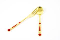 Guld- sked och gaffel som isoleras på vit Arkivbilder