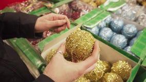 Guld- skinande boll för julgranen i kvinnliga händer Flickan väljer leksaker för det nya året arkivfilmer