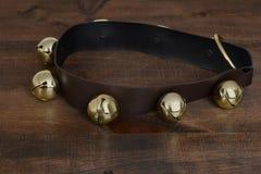 Guld- slädeklockor på trä Royaltyfri Bild