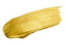 Guld- slaglängd för sudd för målarfärgborste Guld- färgfläck för akryl på vit bakgrund Abstrakt guld som blänker texturerad glans Arkivfoton