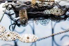 Guld- smycken är gula och olika skuggor Smycken från metalllegeringen med openwork modeller på den reflekterande yttersidan arkivfoto
