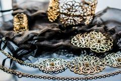 Guld- smycken är gula och olika skuggor Smycken från metalllegeringen med openwork modeller på den reflekterande yttersidan royaltyfria bilder