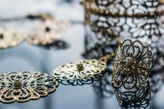 Guld- smycken är gula och olika skuggor Smycken från metalllegeringen med openwork modeller på den reflekterande yttersidan royaltyfri fotografi
