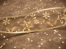 Guld- snöflingaband på guld- bakgrund Arkivbilder