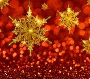 Guld- snöflingor för jul på röd bakgrund royaltyfria foton