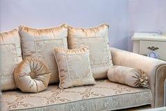 Guld- soffa med kuddar Arkivbild