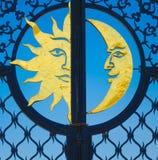 Guld- sol och måne på järnporten Royaltyfri Foto
