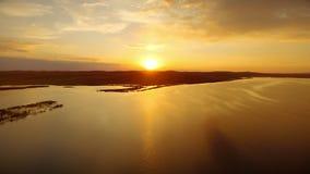 Guld- sol som reflekterar i yttersidaflodvatten under sikt för aftonsolnedgångsurr lager videofilmer