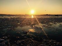 Guld- solnedgång över den djupfrysta floden Royaltyfri Foto
