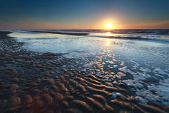 Guld- solnedgång över Nordsjönsandstranden på lågvatten Royaltyfri Bild