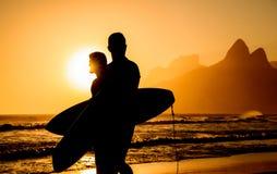 Guld- solnedgång i den Ipanema stranden och två surfarekonturer royaltyfri fotografi
