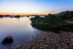 Guld- solnedgång i Porto, Portugal det långa exponeringsskottet på vaggar stranden royaltyfria bilder