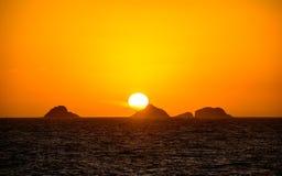 Guld- solnedgång med den stora runda solen, orange vidsträckt himmel, mörk wate arkivfoton
