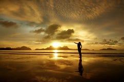 Guld- solnedgång med flickan på ön av El Nido, Filippinerna Royaltyfri Foto