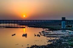 Guld- solnedgång med floden & bron royaltyfri bild