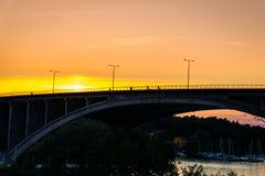 Guld- solnedgång med folk som cyklar på en bro Arkivfoto