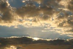 Guld- solnedgång med moln Arkivbild