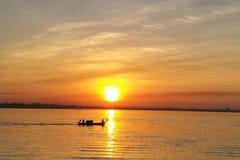 Guld- solnedgång och reflexion på havet med fiskebåten arkivbild