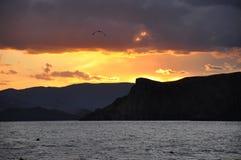 Havssolnedgången målar bakgrundsbergen. Royaltyfri Fotografi