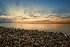 Guld- solnedgång på den steniga stranden på kusten av havet av Japa Royaltyfria Foton