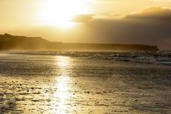 Guld- solnedgång på stranden arkivbilder