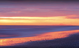 Guld- solnedgång på stranden royaltyfri foto