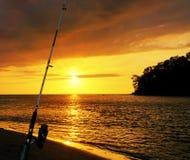Guld- solnedgång på stranden med den fiska polen och aftonglöd Havsreflexionsröda ljuset begreppet kopplar av fotografering för bildbyråer