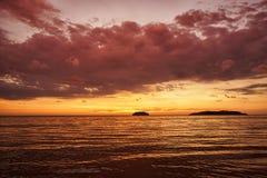 Guld- solnedgång på stranden med mörkt moln och aftonglöd Havsreflexionsröda ljuset som soluppg arkivbild