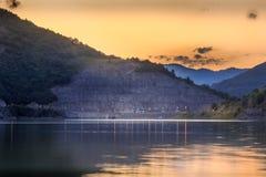 Guld- solnedgånghimmel med fluffiga moln över den reflekterande silkeslena sjön Arkivbilder