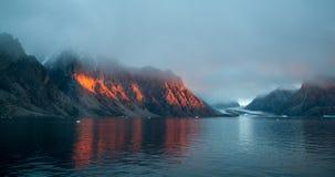 Guld- solnedgångljus på berg, Scoresby Sund, Grönland arkivbilder