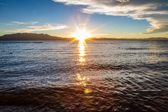 Guld- solstjärnor reflekterar av yttersidan av glas- vatten, medan solen ställer in bak plana berg i avståndet royaltyfria bilder