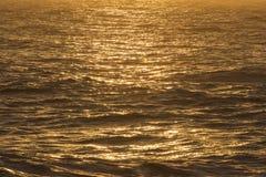 Guld- soluppgånghavbakgrund Arkivbild