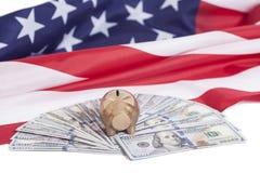 Guld- spargris på hundra dollar med amerikanska flaggan Arkivbild