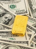 Guld- stänger på dollarräkningar Royaltyfri Foto