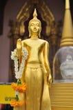 Guld- stående Buddhastaty. Arkivfoton