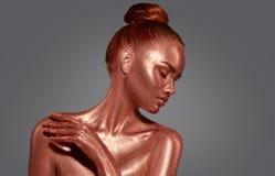 Guld- stående för hudskönhetkvinna Flicka för modemodell med guld- makeup för ferie arkivbild
