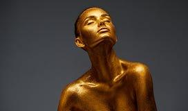 Guld- stående för hudskönhetkvinna Modeflicka med guld- makeup för ferie Kroppkonst Folk med guld- omfamna för smink royaltyfria foton