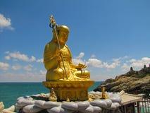 Guld- staty av en gud som sitter vid havet arkivfoton