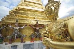 Guld- staty av Kinnorn, jättar och guld- Chedi på Wat Phra Kaew i Bangkok, Thailand Arkivfoto