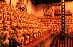 Guld- statyer av Buddha i buddisttempel arkivbilder