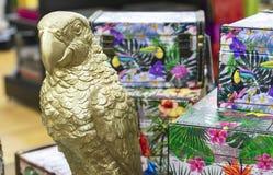 Guld- statyett av en papegoja mot bakgrunden av färgrika bröstkorgar i presentaffären royaltyfri foto