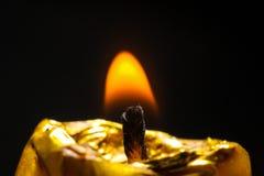 Guld- stearinljusbrännskada på den svarta bakgrundsflamman Arkivfoto