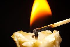 Guld- stearinljusbrännskada på den svarta bakgrundsflamman Royaltyfri Fotografi