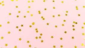 Guld- stjärnastänk på rosa färger festlig ferie för bakgrund celeb Arkivbilder